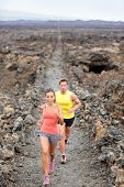 Cross country running woman and man trail runners jogging training outdoors for marathon or triathlo