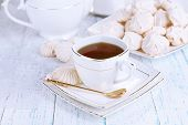 Cup of tea with meringues on table close-up