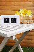 Digital alarm clock on table, on wooden background