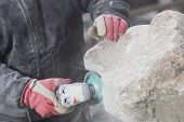 sculptor working on a large stone sculpture