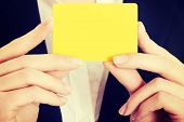 Empty yellow card in business woman's hands.