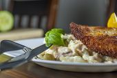 picture of wieners  - Wiener schnitzel with potato and vegetables salad on wood table - JPG