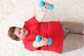 Large fitness man making exercises with dumbbells on floor, at home
