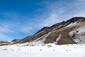 Volumetric landscape of mountains in early spring. Snowy trail