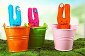Funny handmade Easter rabbits in pails, on green grass