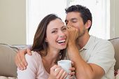 Young man whispering secret into a cheerful young womans ear in the living room at home
