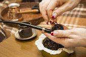 foto of tobacco-pipe  - Female hand tamping tobacco smoking pipe - JPG