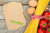 Pasta, tomatoes, eggs and blank brown paper for copy space on wooden table background