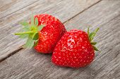Ripe strawberries over wooden table background closeup