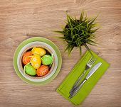 Easter eggs with silverware and potted flower over wooden table background