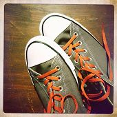 Instagram style image of a pair of sneakers with orange shoe laces on wood surface