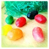 Instagram style image of jelly beans and fake plastic easter grass