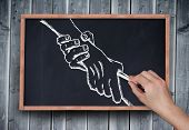 Composite image of hand drawing handshake with chalk on chalkboard on grey wooden planks