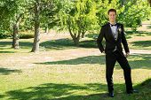 Full length portrait of confident groom standing in garden