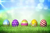 picture of easter candy  - Colourful easter eggs on the grass under sunny sky - JPG