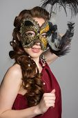 Woman in carnival mask on gray background.