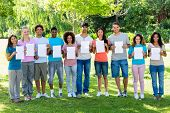 Group portrait of multiethnic friends holding blank papers while standing in park