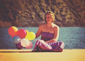 a young woman sitting on a dock with balloons done with a retro vintage instagram filter