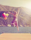a carefree young woman jumping on a dock with balloons done with a retro vintage instagram filter