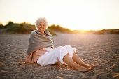 Happy Old Woman Relaxing On The Beach