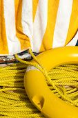 Yellow Life Buoy, Rope And Towel On A Pier