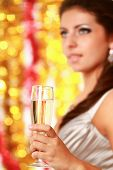 Beautiful young brunette woman drinking champagne at christmas party. Isolated on decorated backgrou