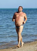 fitness - overweight man running on sea coastline