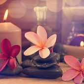 Spa setting with frangipani flower, essential oil, zen stones and aromatic candles on table, Zen con