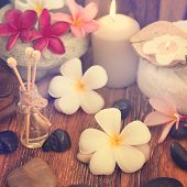 Spa treatment setting with frangipani ,pure essential oil and burning candle, vintage toned style.