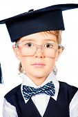 Portrait of a cute smart boy wearing suit and academic hat. Educational concept. Isolated over white