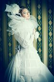 Beautiful fashion model in the refined white dress and elegant hat. Vintage style. Art project.