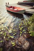 Red boat at wooden dock on lake in cottage country with foreground of rocks and plants
