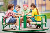 Image of joyful friends having fun on carousel outdoors