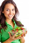 Pretty young girl holding bowl of fresh vegetable salad and looking at camera