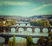 Vintage retro hipster style travel image of travel Prague concept background - elevated view of bridges over Vltava river from Letna Park. Prague, Czech Republic with grunge texture overlaid