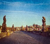 Vintage retro hipster style travel image of Charles bridge and Prague castle in the early morning wi