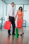 Happy executive couple with shopping bags in office
