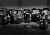 stock photo of kettlebell  - Kettlebells weights in a workout gym in black and white - JPG