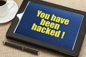 you have been hacked - text with a binary background  on a digital tablet