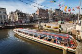 Sightseeing boat goes through the canal in historical central part of Amsterdam