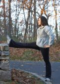 pic of hamstring  - Pretty young woman stretching leg outdoors in park - JPG