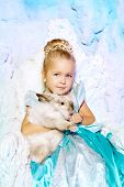 Little girl in princess dress on a background of a winter fairy tale. Baby snow queen. Sweet smiling