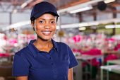 stock photo of blue-collar-worker  - pretty young african female blue collar worker inside clothing factory - JPG