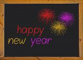 Happy new year written on a small blackboard with a wooden frame