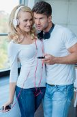 Young Couple in White and Blue casual Attire Listening Music on Mobile Phone So Sweet