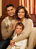 Family in warm cashmere clothes in home interior