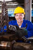happy young male industrial mechanic at work