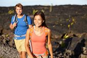 Hiking people - couple walking on lava field on Hawaii. Tourists hikers on hike near Kilauea volcano
