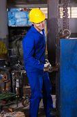 manual worker using big hammer in workshop