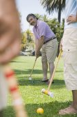 Hispanic man playing croquet